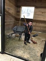 Boy working in a stable in Horse SenseAbility's Stable Moments program