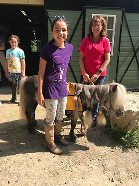 Smiling child and adult standing next to a pony