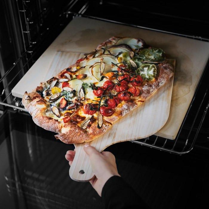 Pizzastein mit Pizza im Ofen