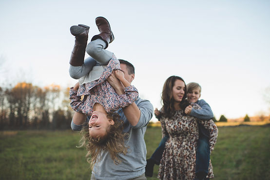 Family of 4 playing in a field
