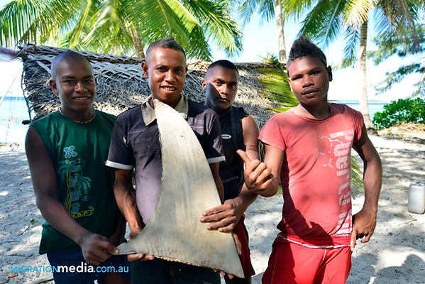 Yong men pose with the fin cut off a hammerhead shark