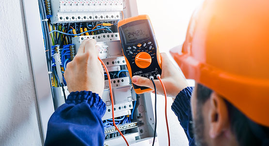 Electrician installing electric cable wires and fuse switch box. Multimeter in hands of el