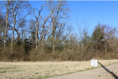 The site of the proposed development with a sign informing passersby of the rezoning application.