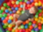 pretty-baby-boy-having-fun-at-a-ball-pit