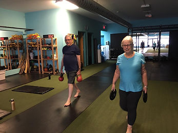 two elderly people performing lunges