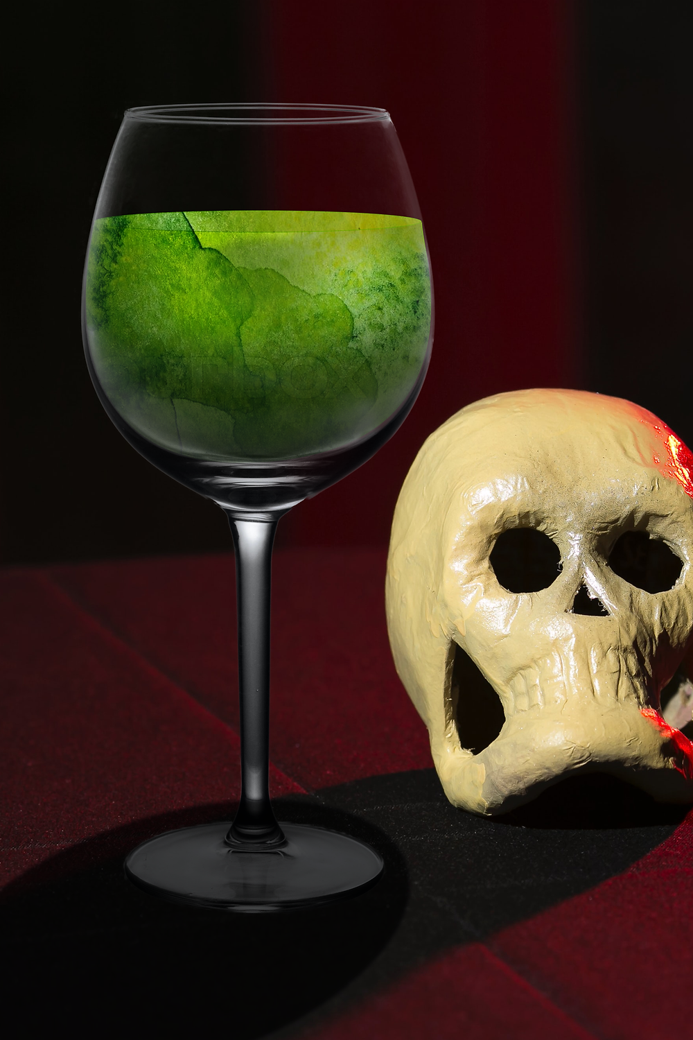 A wine glass with a disturbing green liquid next to a white paper maché skull on a red tablecloth