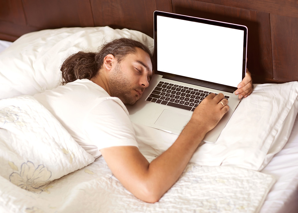 A man with long hair sleeps holding his computer on the pillow in a bed with white linens