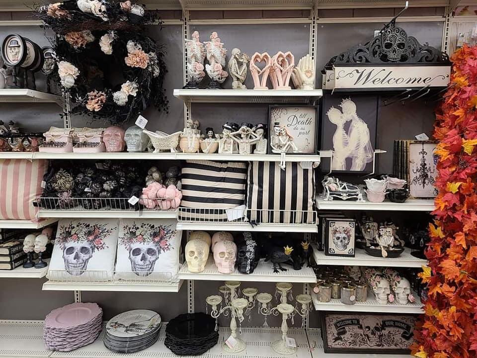 Shelves full of spooky black, pink, and white Halloween decor
