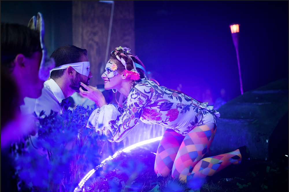 A kneeling woman in harlequin tights, a floral body suit, and a face paint masquerade mask holds the chin of a bearded man with a white cloth eye mask.