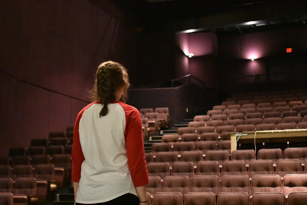 Young woman in an empty theatre