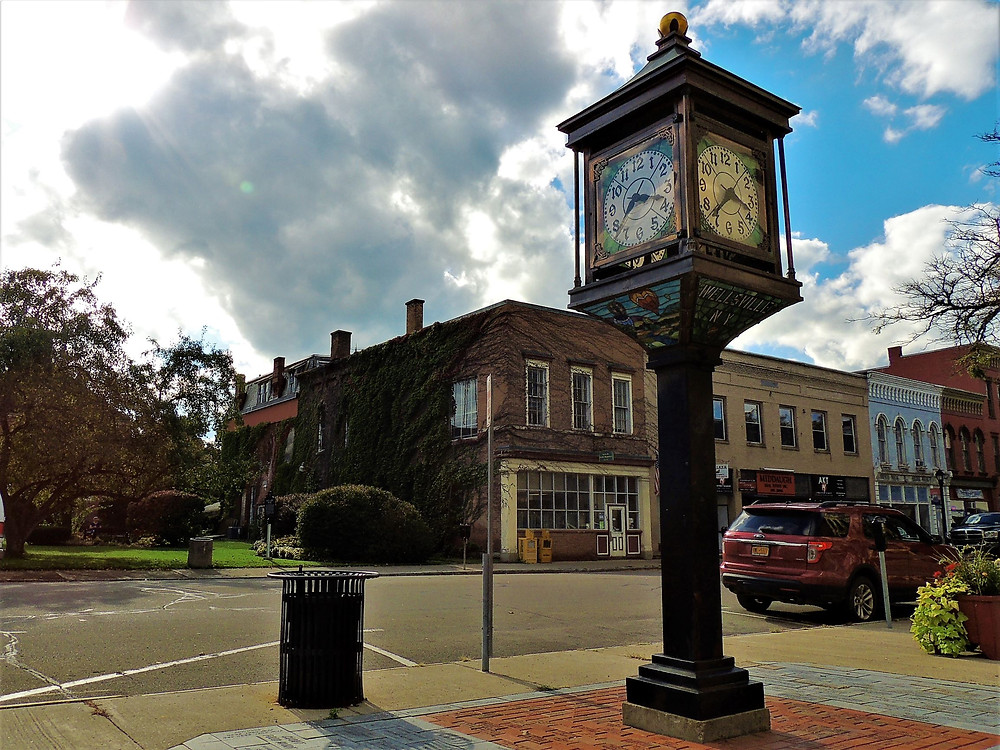 An image of a quaint old-fashioned main street in Wellsville, NY. The Stained-Glass Clock stands against a background of blue sky and clouds.