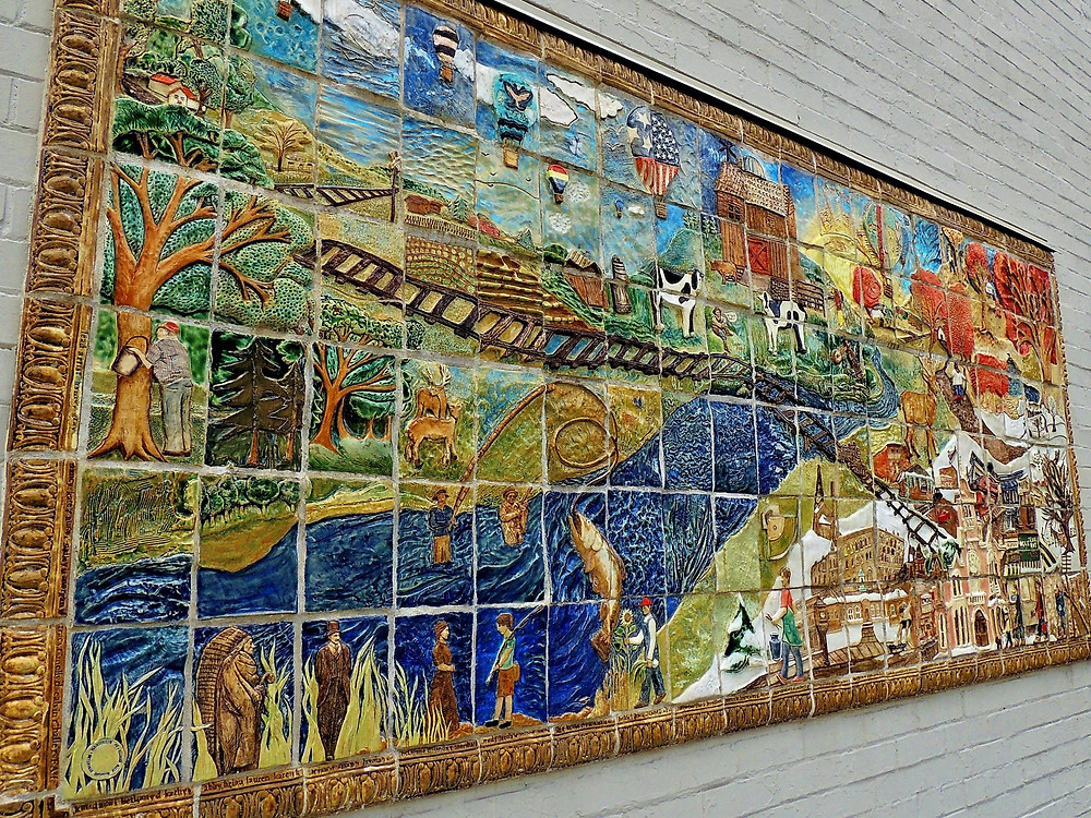 A large art piece on the side of a building in Wellsville NY. Made up of a mosaic of hand-crafted tiles. Features the activities and history of the region, including images of maple-tapping, air balloons, fishing, cows grazing, and a railroad going through it all.