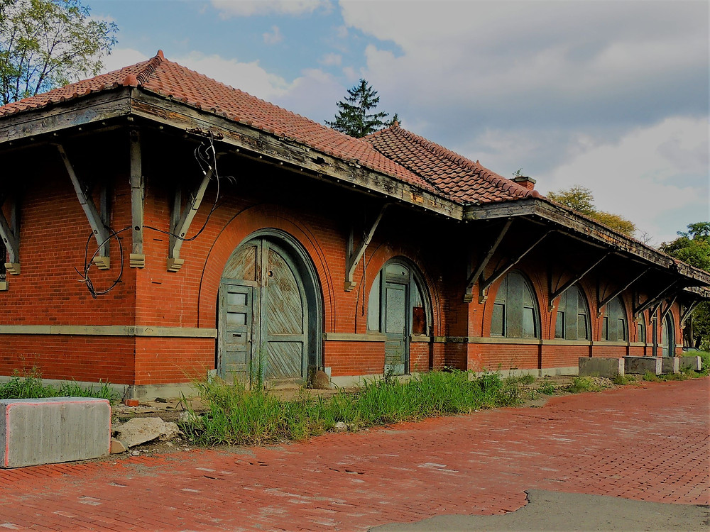 Train Depot with a terra cotta tile roof, brick exterior, and brick street in the foreground.