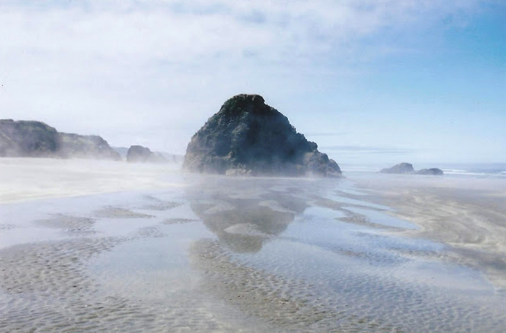 A dreamy beach with a large rock formation and low tide