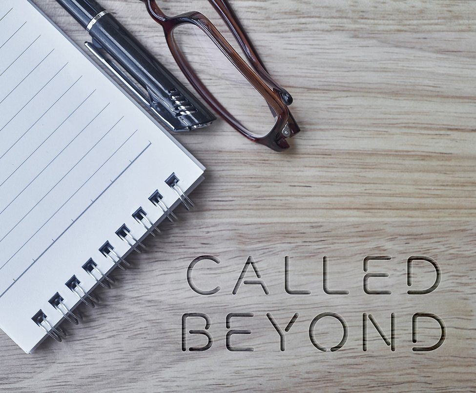 Called Beyond engraved on wooden desk, with notepad, glasses and pen