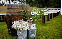 Wine barrel and wood benche add rustic charm to a wedding ceremony site.