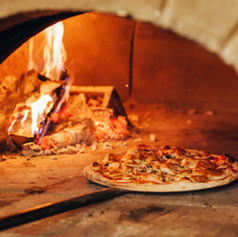 Italian pizza is cooked in a wood-fired