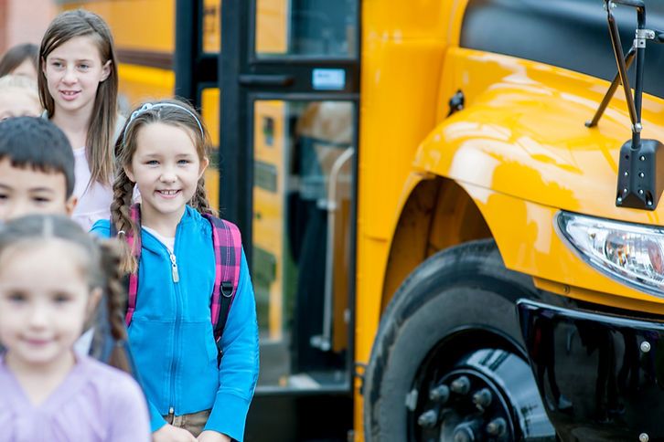 Children smiling as they arrive at school with yellow bus in the background