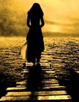 Lady standing at end of pier, looking at sunset over a lake