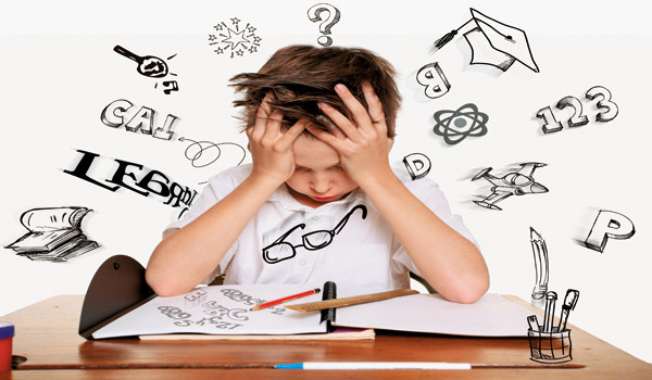 A boy sitting down at a desk with his head in his hand and all words and symbols around him