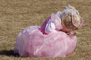 girl dressed in a pink princess dress crying