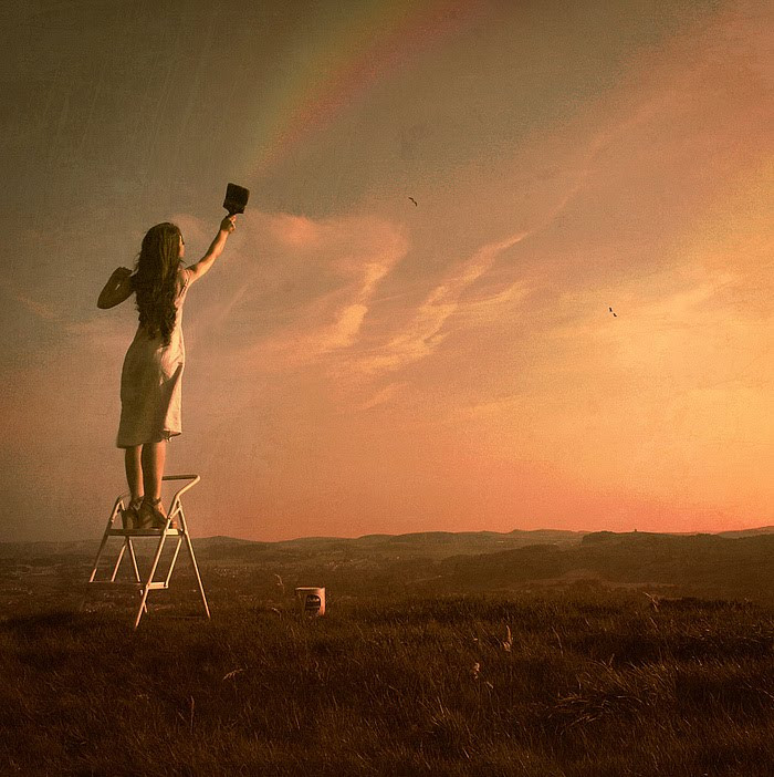 A girl standing on a ladder painting a rainbow in the sky.