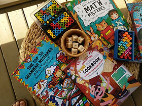A basket is holding The Top 30 Grammar Mistakes, Yum-Schooling Cookbook, and Fun-Schooling Math Mysteries
