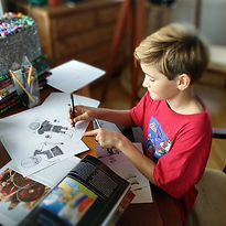 A young boy homeschooling drawing pictures of monsters at a desk