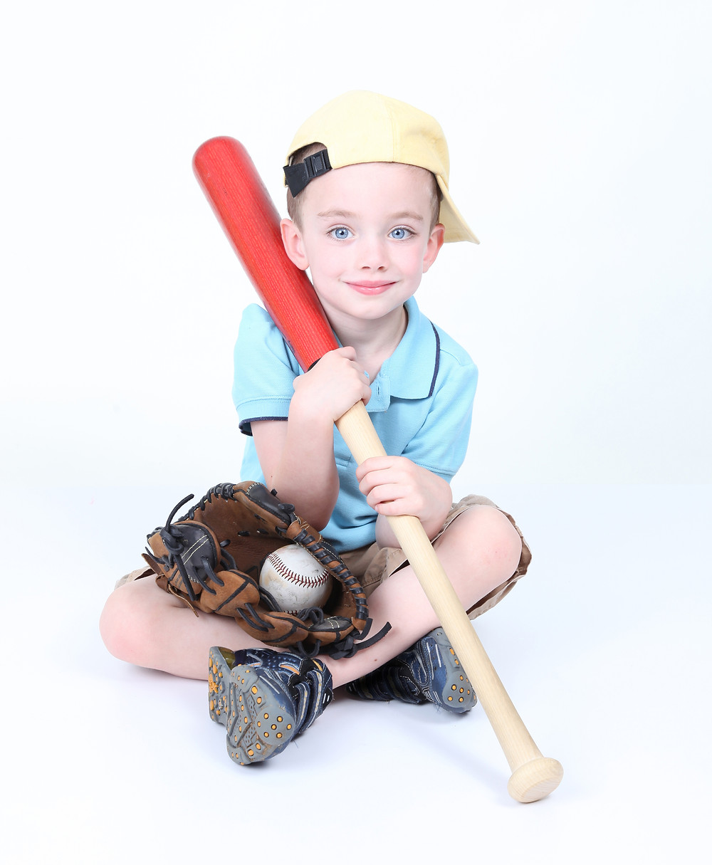Young Boy Holding A Baseball Bat With Ball And Glove.jpg
