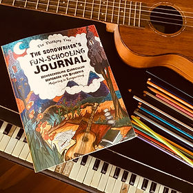 The Songwriter's Fun Schooling Journal sits next to a piano and guitar