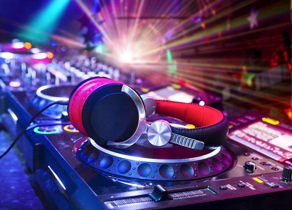 Dj mixer with headphones at nightclub.