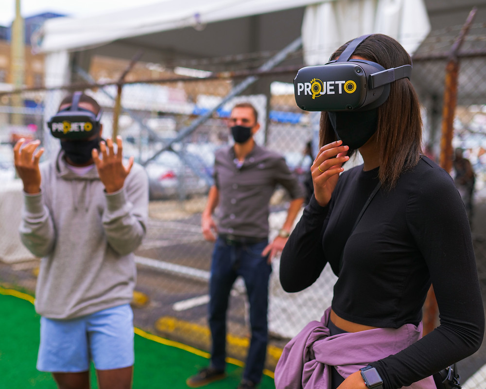 Two young adults wearing virtual reality headsets look around while another person watches in the background