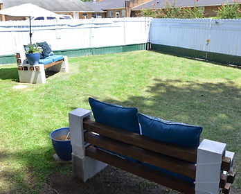 Cushioned benches located in the large private backyard