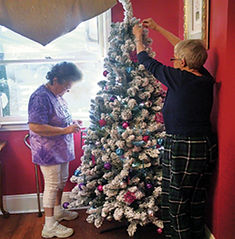 Residents enjoy decorating the holiday tree at Christmas time