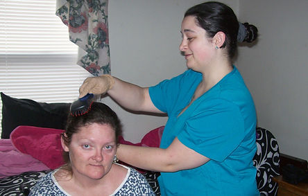 Caregiver brushing a resident's hair. Assisting residents with everyday care is an important part of caregiving.