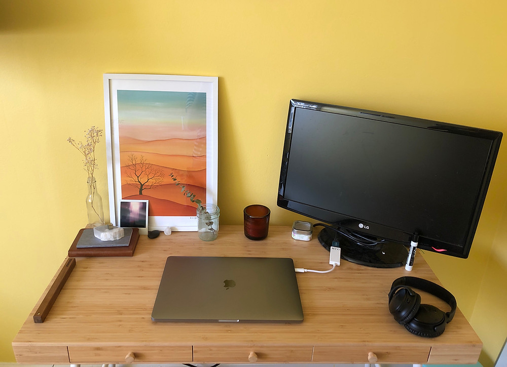 A laptop sits on a desk in a yellow room.
