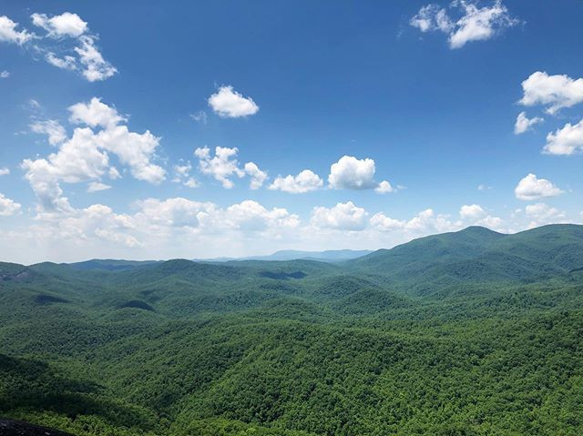 (Landscape view of the Blue Ridge mountains in North Carolina; mountains covered in green trees, with a blue sky dotted with clouds above.)