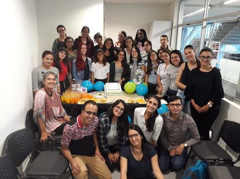 Grupo de estudiantes del semillero Piencias junto a la torta del cumpleaños de los tres años del semillero.