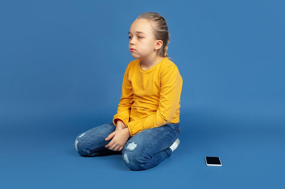 portrait-sad-little-girl-sitting-isolate