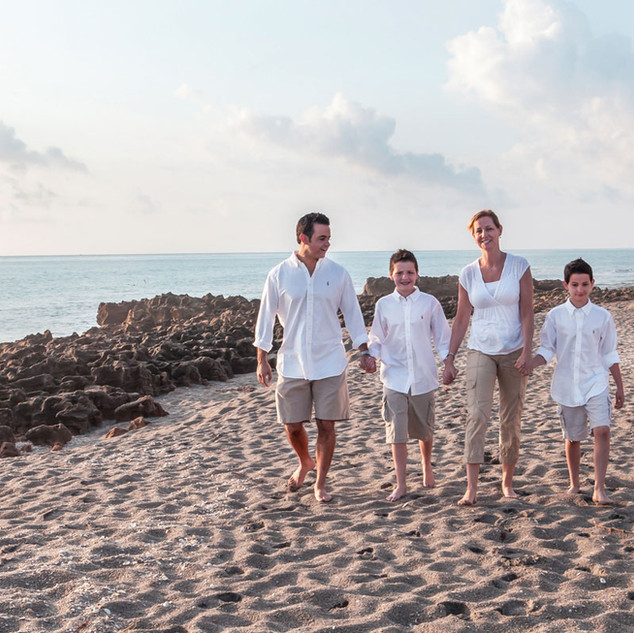 portrait of family on beach wearing white
