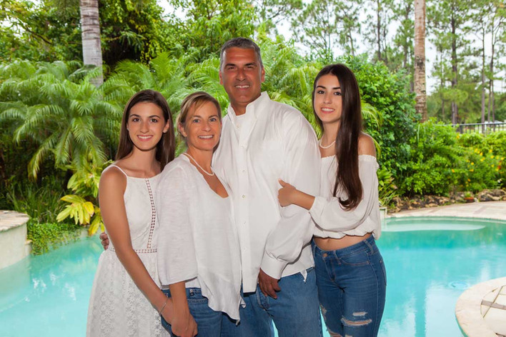 family wearing white in front of pool