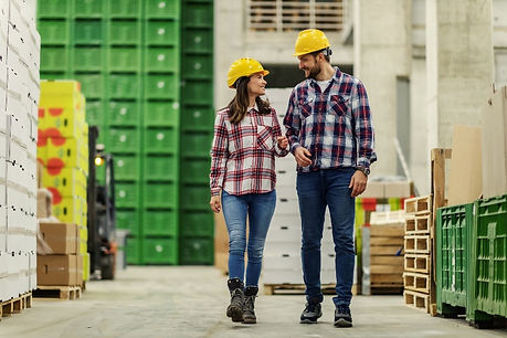 the-man-and-woman-with-helmet-pass-through-the-factorys-wide-and-modern-warehouse (1).jpg