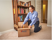 Moving company employee packing books into boxes