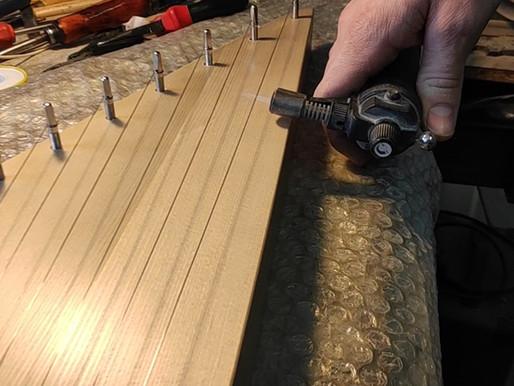 Kā uzlikt stīgu koklei ar metāla tapām.
