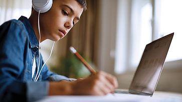 young boy doing homework on laptop.jpg