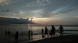 Fishermen on beach at sunset.-349