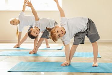 Little children practicing yoga indoors.