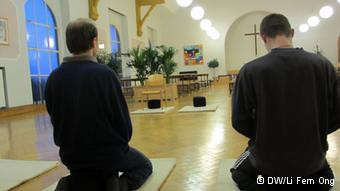 Inside the church hall two prisoners meditate in silence in one of the twice weekkly meditation sessions for inmates at Siegburg prison.