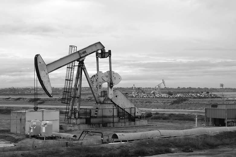 black and white photo of oil derrick wit