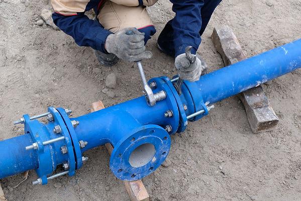 Workers installing water supply pipeline